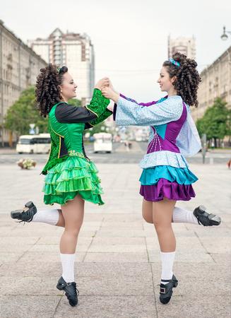 Two women in irish dance dresses and wig dancing outdoor photo