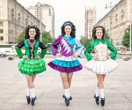Three women in irish dance dresses and wig posing outdoor photo