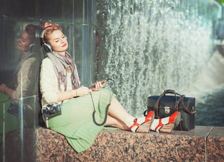 Hipster fashion girl in green skirt listening music outdoor photo