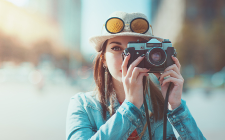 Hipster girl in hat and glasses making picture with retro camera outdoor. Focus on camera Standard-Bild