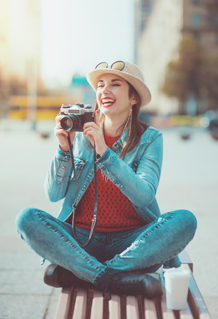 Young beautiful hipster girl with retro camera in the city