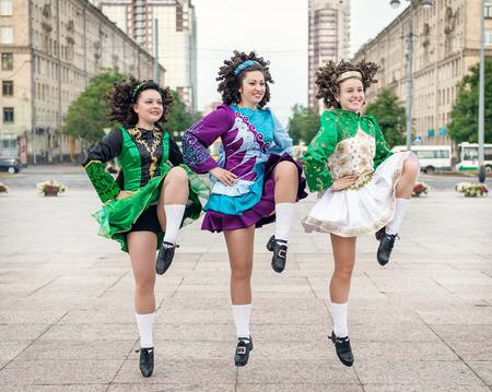 Three women in irish dance dresses and wig dancing outdoor