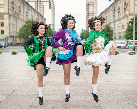 Three women in irish dance dresses and wig dancing outdoor