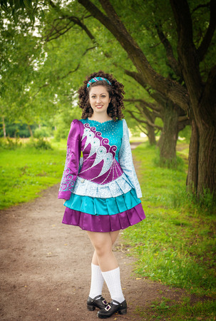 Young beautiful girl in irish dance dress and wig posing outdoor photo