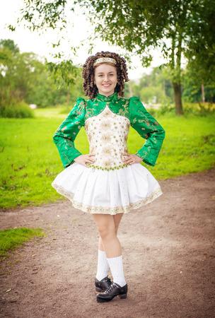 Young beautiful girl in irish dance dress and wig posing outdoor photo