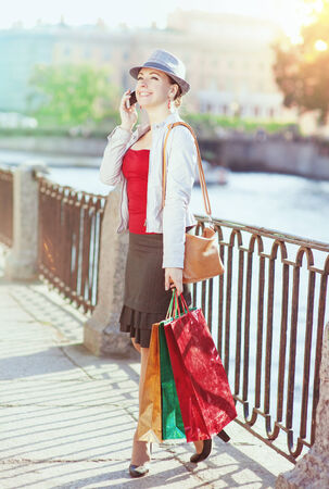 Beautiful girl with shopping bags talking on the mobile phone in the city photo