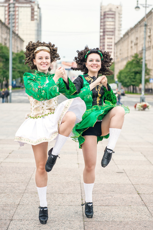Two women in irish dance dresses and wig dancing outdoor photo