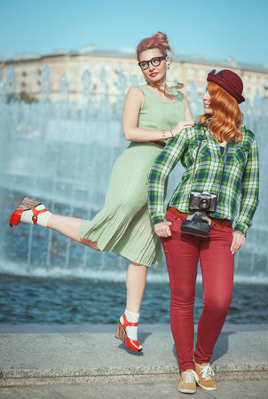 Two beautiful hipster girls with retro camera outdoor photo