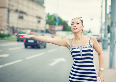 hailing: Young beautiful woman dressed striped dress trying to hail a cab in the city