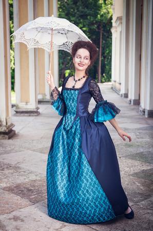 medieval dress: Joven y bella mujer en vestido medieval azul con paraguas al aire libre Foto de archivo