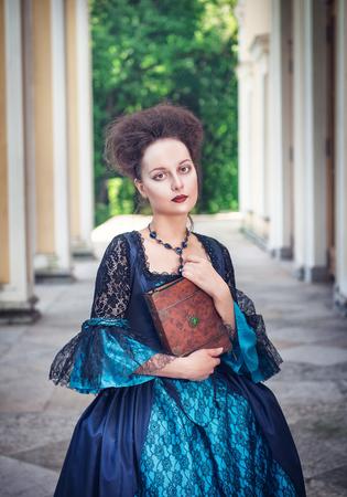 medieval dress: Joven y bella mujer en vestido medieval azul con el libro al aire libre