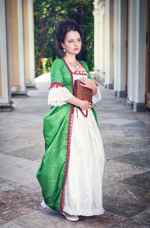 ruche: Beautiful young woman in green medieval dress with book outdoor