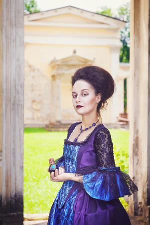 medieval dress: Joven y bella mujer en vestido medieval azul con la botella de perfume al aire libre Foto de archivo