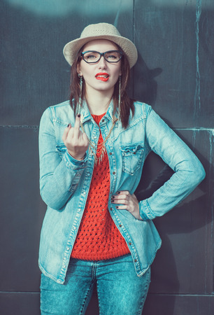Young beautiful girl in red jersey and hat showing middle finger outdoor near wall photo