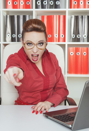 Angry woman boss in eyeglasses pointing out at someone Stock Photo