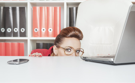 Business woman with glasses hiding behind table and afraid