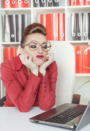 unmotivated: Boring business woman in glasses working at office Stock Photo