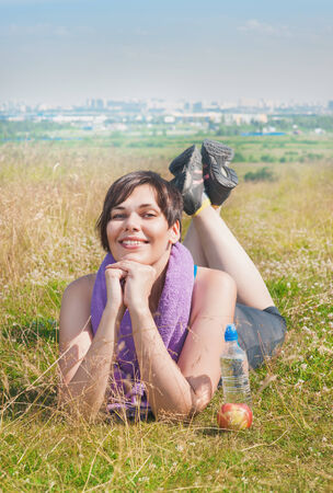downshifting: Beautiful plus size woman with towel lying on the meadow outdoor in summer