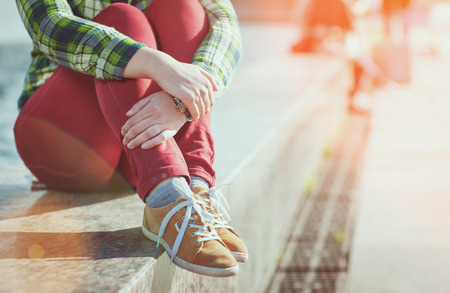 Yellow sneakers on girl legs in hipster style sitting on the bench Stock Photo