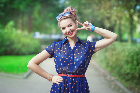 summer dress: Beautiful young woman in fifties style with braces winking outdoor Stock Photo