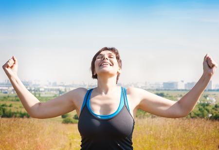 Gelukkig mooie succesvolle plus size vrouw verhogen armen naar de hemel in de zomer openlucht Stockfoto