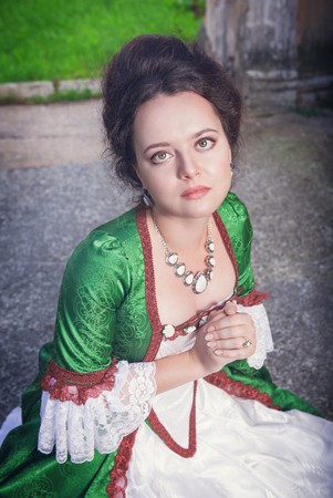 ruche: Beautiful young medieval woman in green dress praying outdoor Stock Photo