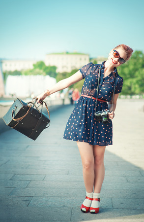 fifties: Beautiful young woman in fifties style with braces holding retro camera outdoor