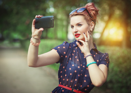 Beautiful young woman in fifties style taking picture of herself outdoor photo