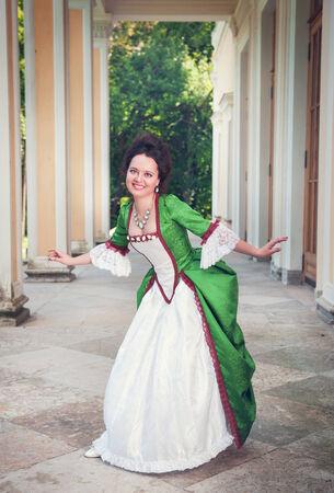 vestido medieval: Joven y bella mujer en traje medieval verde haciendo reverencia al aire libre