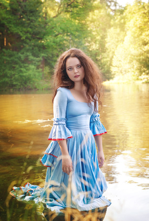 Beautiful young woman with long medieval dress standing in the water outdoor Stock Photo