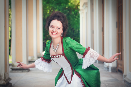 ruche: Beautiful young woman in green medieval dress doing curtsey outdoor