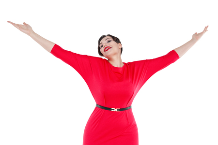 size: Happy beautiful plus size woman in red dress with hands up  isolated on white background
