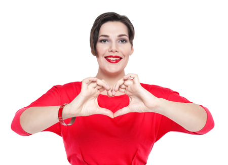 Beautiful plus size woman doing a heart shape with her hands isolated. Focus on hands photo