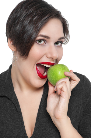 Beautiful plus size woman with green apple isolated on white background photo