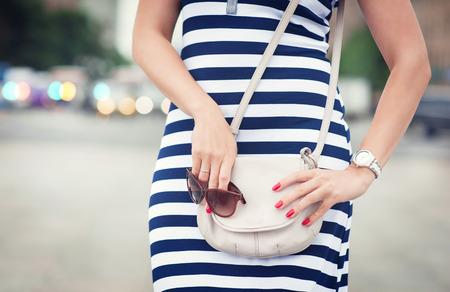 Modieuze vrouw met witte tas in haar handen en gestreepte jurk in de stad Stockfoto