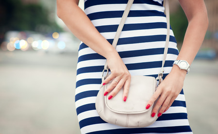 fashion bag: Fashionable woman with white bag in her hands and striped dress in the city