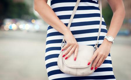 mujeres elegantes: Mujer de moda con bolsa blanca en sus manos y vestido de rayas en la ciudad Foto de archivo