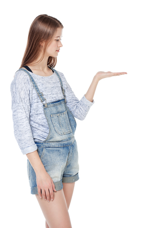 Young fashion teenage girl looking on her palm isolated on white background photo
