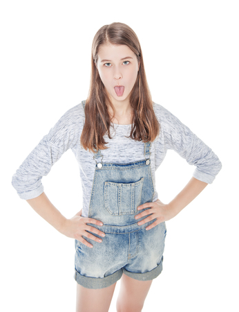 overalls: Young fashion girl in jeans overalls showing tongue isolated. Top view Stock Photo