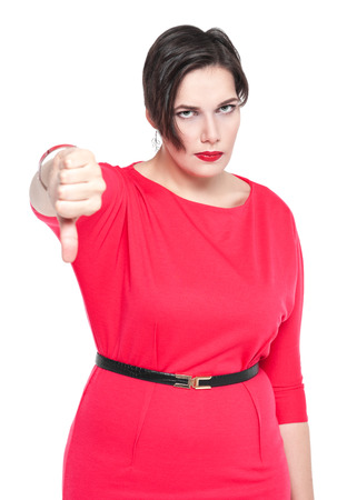 disapproval: Beautiful plus size woman in red dress with thumbs down gesture isolated on white background