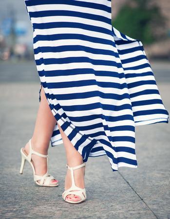 fluttering: Legs of woman dressed long fluttering striped dress outdoor in the city