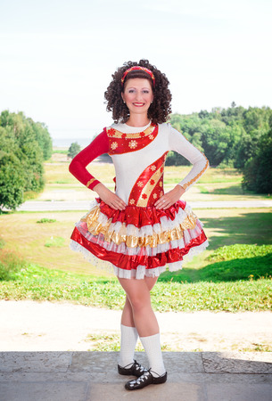 Young woman in red and white irish dance dress and wig posing outdoor photo