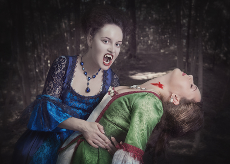 Beautiful vampire woman in blue medieval dress and her victim outdoor