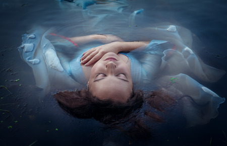 Hermosa mujer ahogada joven en el vestido de color azul situada en el exterior de agua Foto de archivo - 36927259