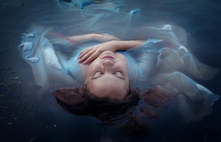 Jonge mooie verdronken vrouw in blauwe jurk liggend in het water buiten