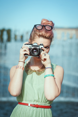 outdoor photo: Beautiful young girl in vintage clothing making picture with retro camera outdoor
