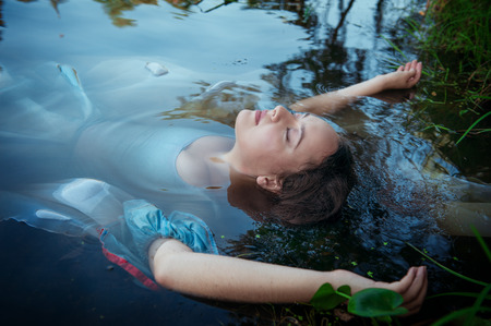 murder scene: Young beautiful drowned woman in blue dress lying in the water outdoor
