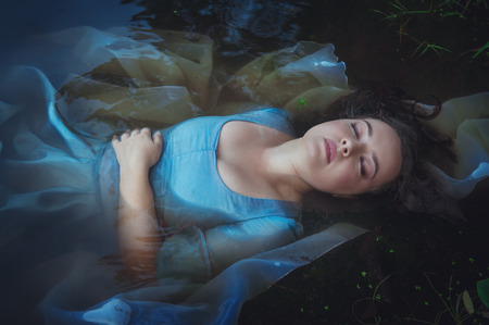 corpse: Young beautiful drowned woman in blue dress lying in the water outdoor