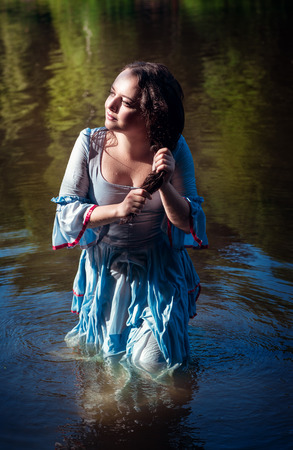long lake: Young beautiful girl in long blue dress standing in the river outdoor