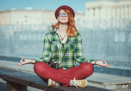 yoga pants: Hipster redhead woman in hat and glasses doing yoga on the bench in the city